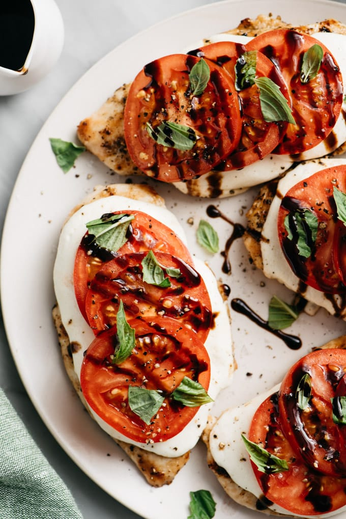 A platter of caprese chicken with tomato, basil, and mozzarella on marble table.