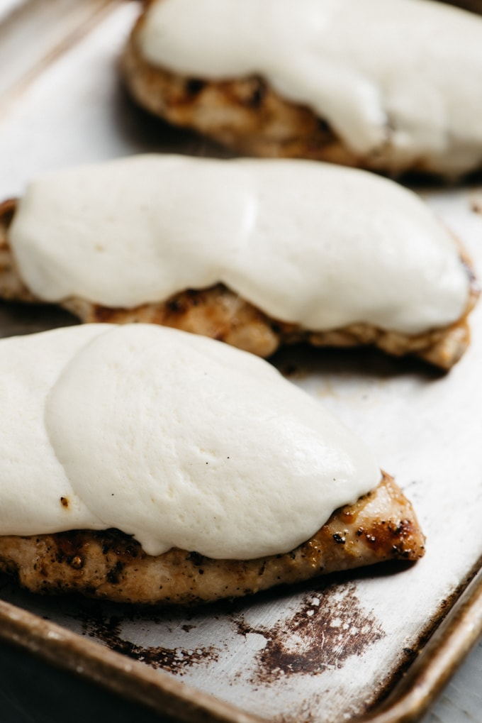 Melted mozzarella cheese on top of grilled italian chicken breats.