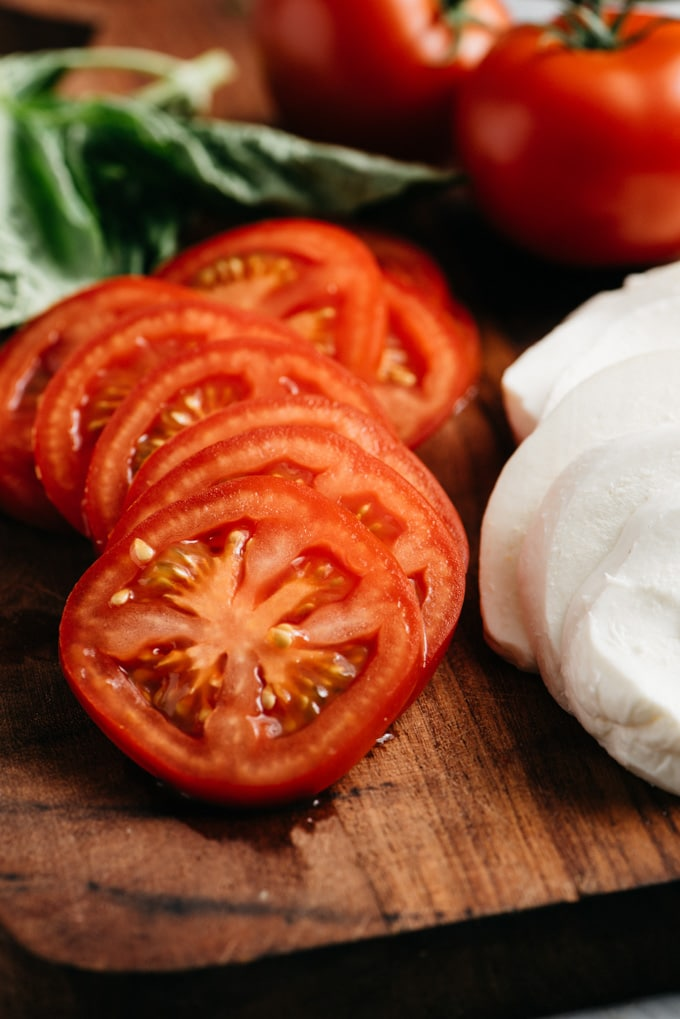 Fresh tomato and mozzarella slices on a cutting board next to a bunch of fresh basil.