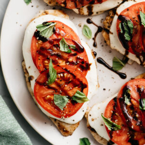 A platter of grilled italian caprese chicken drizzled with aged balsamic vinegar.