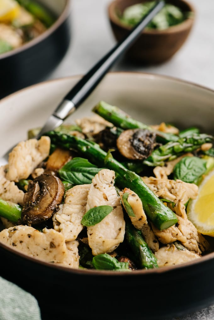 Whole30 chicken and asparagus dinner recipe in a bowl with a black handled fork.