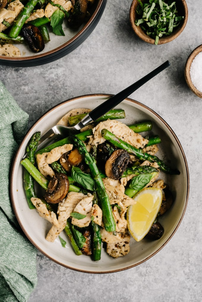 A bowl of chicken and asparagus skillet recipe with a fork and green napkin.
