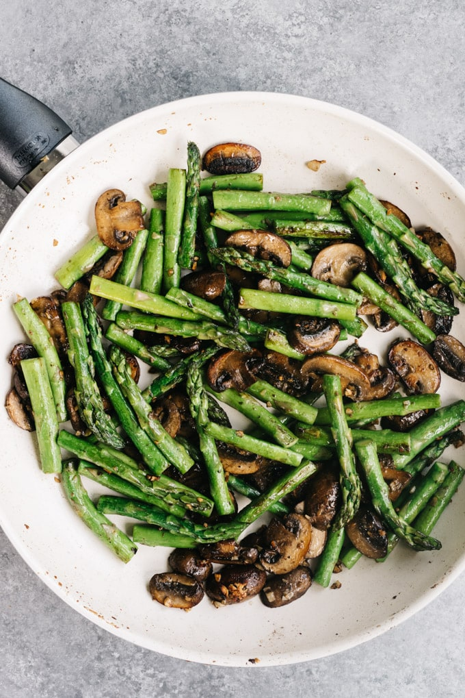 Sautéed asparagus and mushrooms with garlic in a skillet.