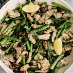 Lemon garlic chicken and asparagus recipe in a skillet with lemon wedges and fresh basil.