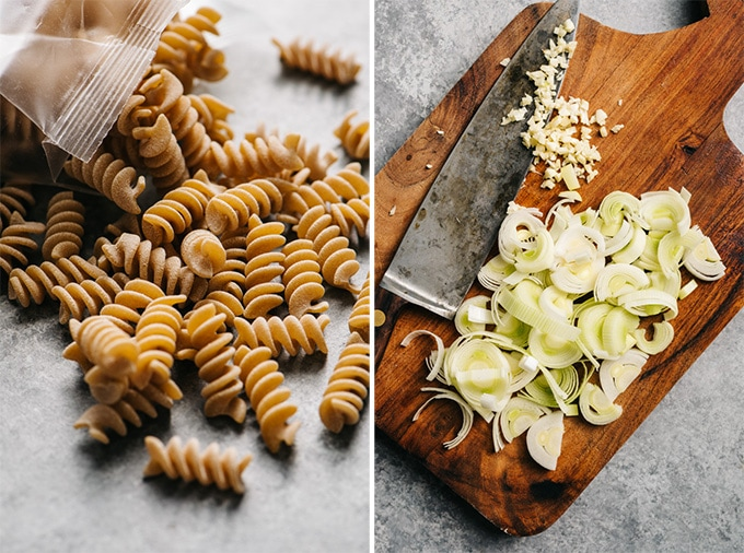 Raw fusilli pasta on a tabletop, and sliced leeks and minced garlic on a cutting board with chef's knife.