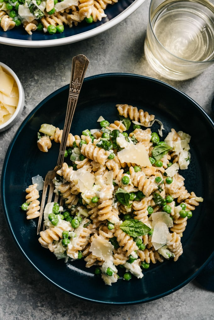 A bowl of ricotta pasta with peas with a glass of white wine and a side of parmesan cheese.