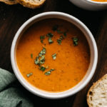 A bowl of roasted tomato soup garnished with fresh basil with slices of sourdough bread on the side.