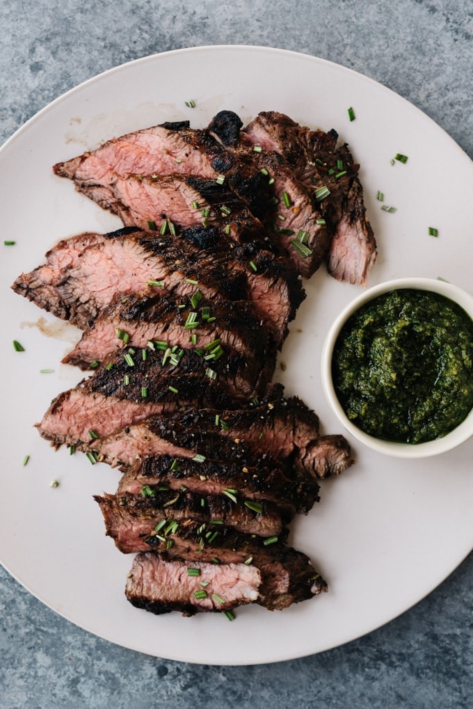 From above, thin slices of rosemary steak on a white plate with a side dish of fresh pesto.