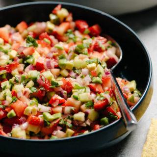 A blue bowl of strawberry avocado salsa with a silver spoon.