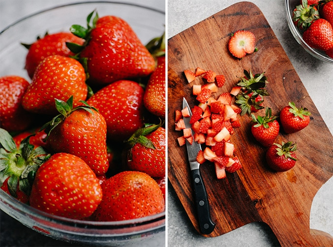 A bowl of fresh strawberries, and diced strawberries on a cutting board.