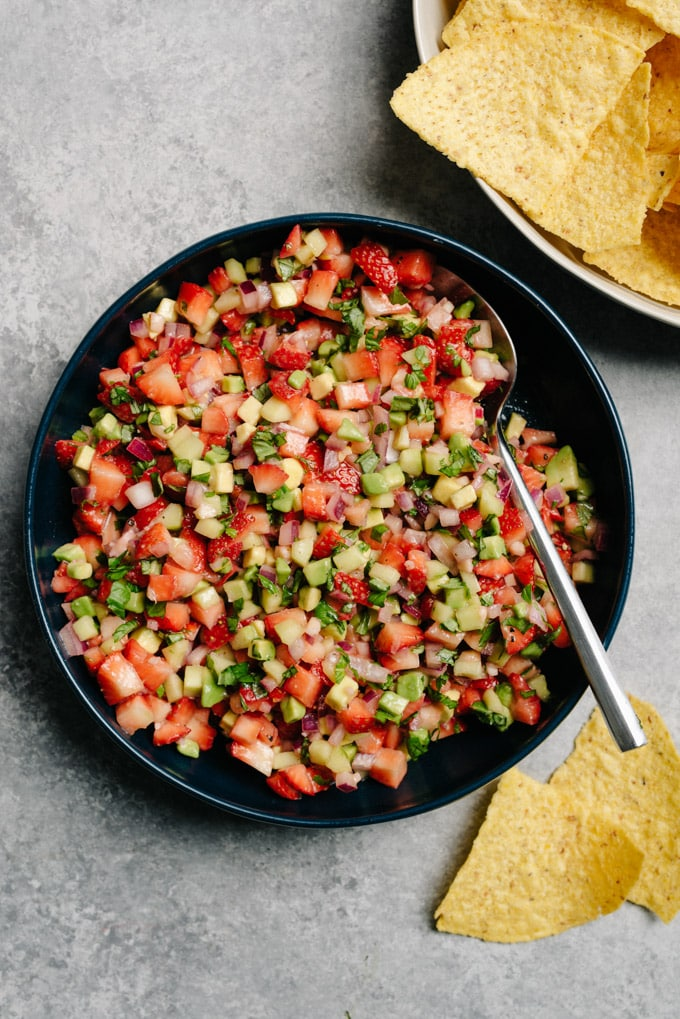 A bowl of strawberry avocado salsa surrounded with tortilla chips.