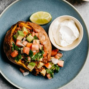 A baked sweet potato stuffed with ground beef taco meat and topped with pico de gallo and avocado.