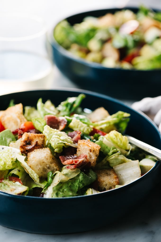 From the side, a bowl of BLT salad with avocado and hot bacon dressing.