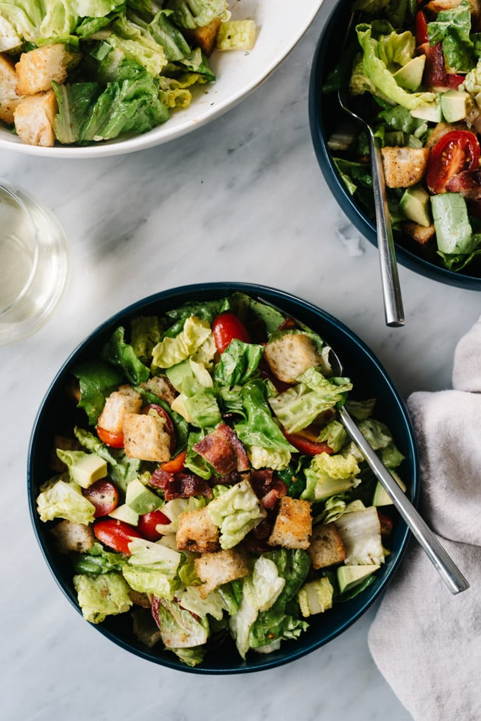 Two bowls of BLT Salad with avocado and hot bacon dressing on marble table with a glass of white wine.
