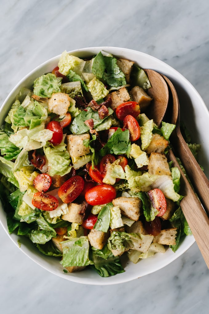 From above, a tossed BLT salad with hot bacon dressing in a white bowl with wood salad spoons.