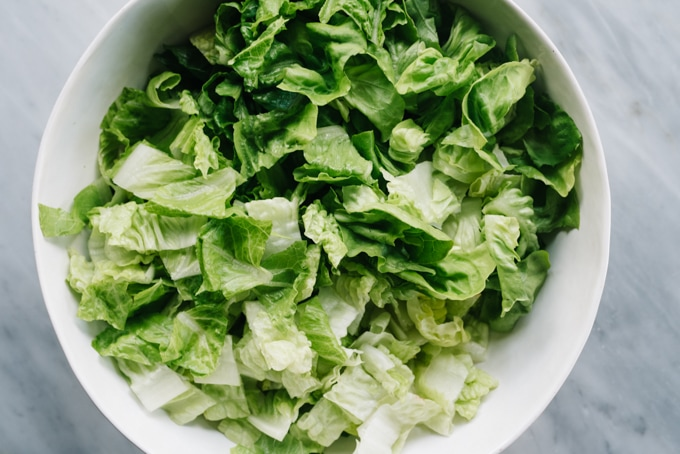 From above, a white salad bowl filled with chopped romaine lettuce and chopped butter lettuce.