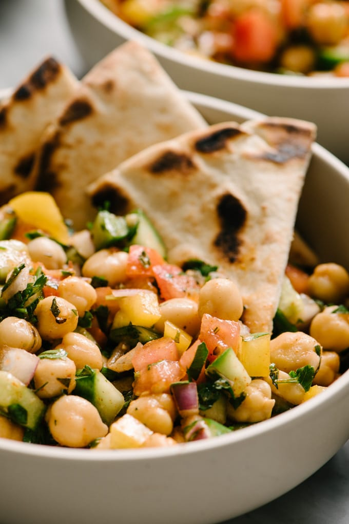 A bowl of mediterranean chickpea salad with several slices of pita bread tucked into the bowl.