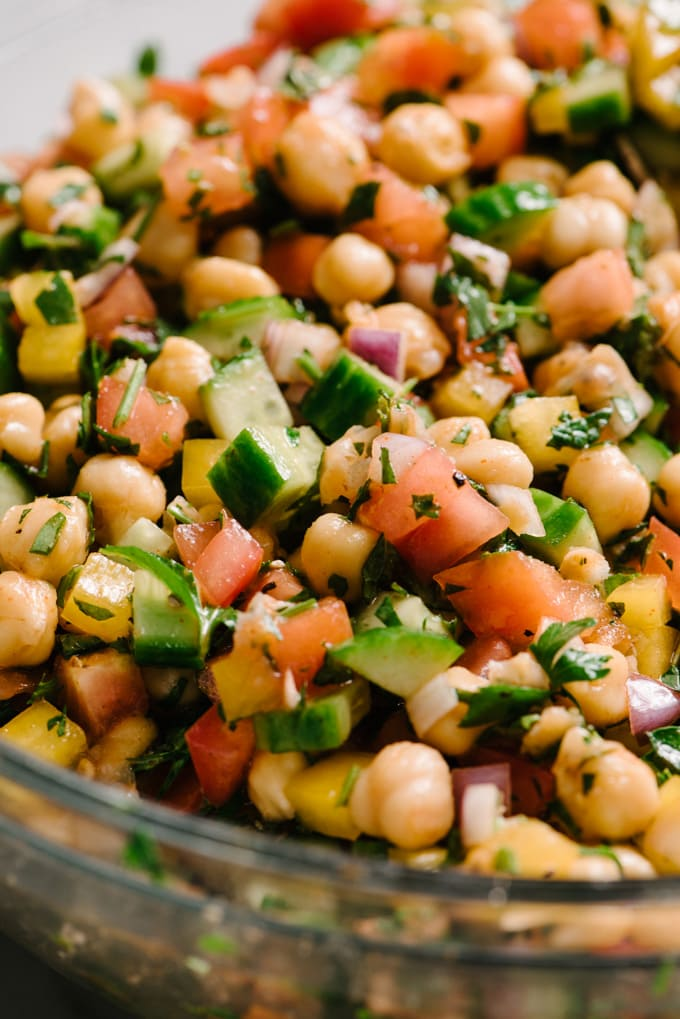 A close-up image mediterranean chickpea salad showing the individual ingredients - marinated chickpeas, cucumber, tomato, bell pepper, red onion, mint, and parsley.