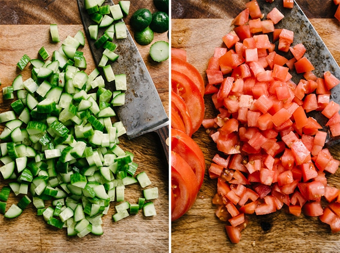 Diced persian cucumbers and diced tomatoes on a cutting board.