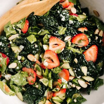 A large white serving bowl filled with strawberry kale salad and wood serving spoons.