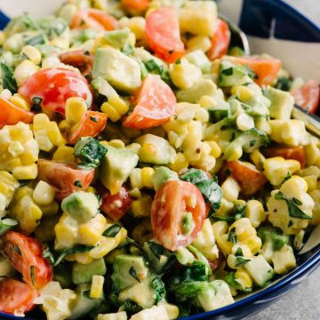 Side view, tomato corn salad with avocado, basil, and buttermilk vinaigrette in a blue and white bowl on a concrete surface with a side dish of dressing.