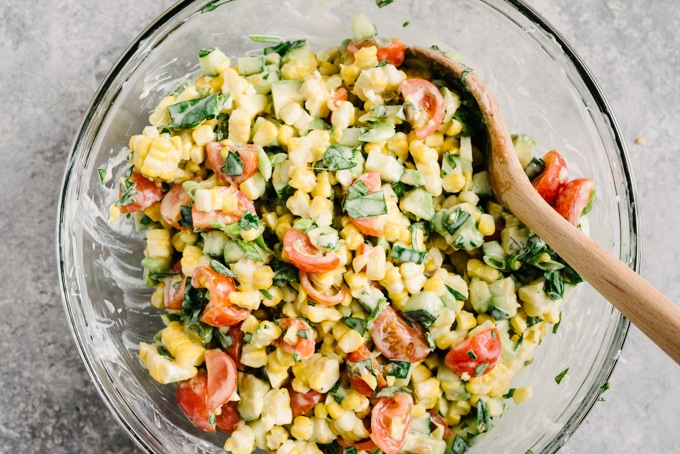 Overhead, tomato corn salad with buttermilk dressing in a glass mixing bowl with a wood spoon.