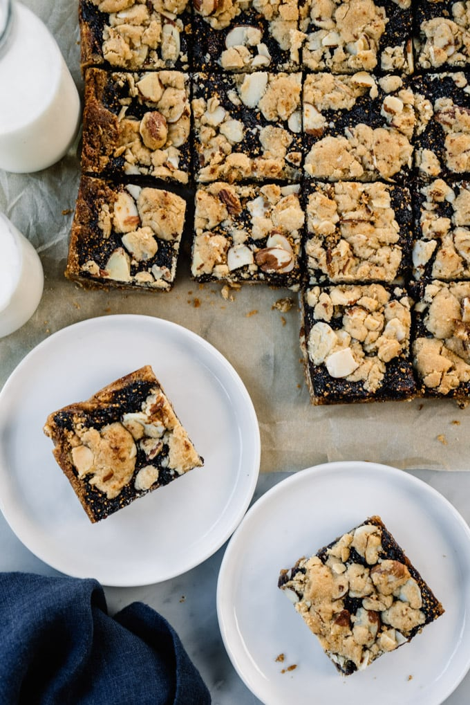 A block of fig bars cut into individual squares with 2 fig bars on white plates.