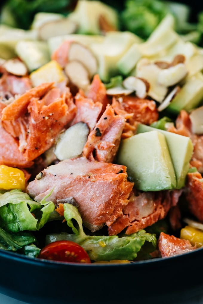 From above, detail shot of flaked salmon and sliced avocado over a bed of salad greens with lemon dressing.