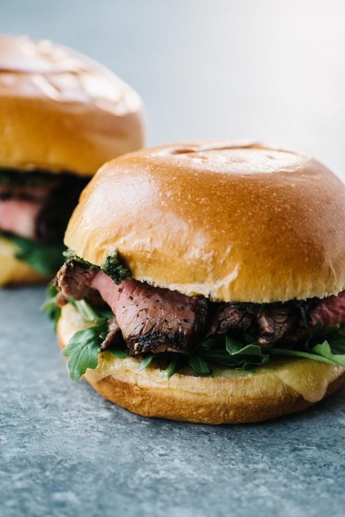 Two steak sandwiches layered with sharp cheddar, arugula, and pesto on a brioche bun.