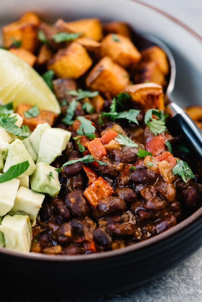 Side view, close up of citrus black beans in a vegan black bean buddha bowl.