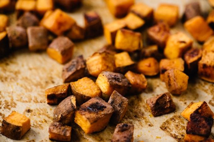 Seasoned roasted sweet potatoes on a baking sheet.
