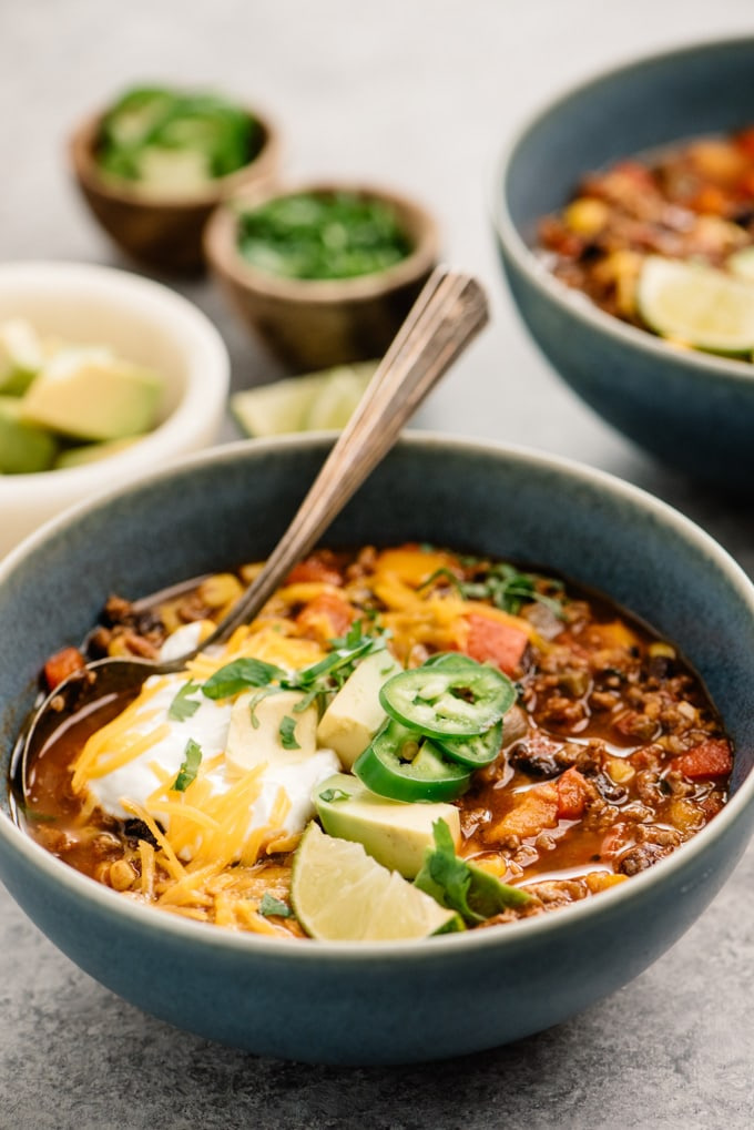 Side view, a bowl of taco soup topped with avocado, sour cream, cheddar, jalapeno, cilantro, and a lime wedge.