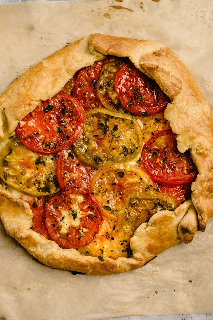From above, a savory tomato galette on a baking sheet fresh from the oven.