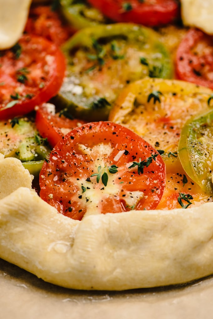 Side view, an unbaked savory galette layered with cheese and heirloom tomatoes.
