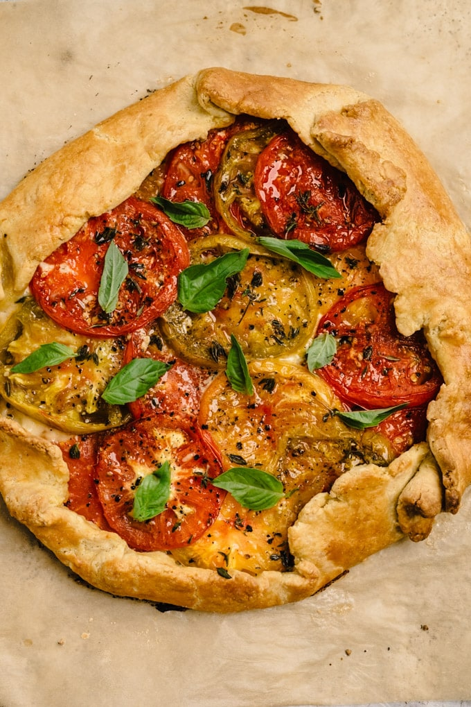 A baked heirloom tomato galette sprinkled with fresh basil.