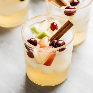 Apple cider sangria cocktails with a cinnamon sugar rim on a marble table with a pitcher of sangria and a smaller jar of cinnamon sticks.