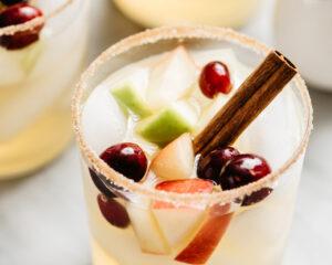 Apple cider sangria served in a rocks glass with a cinnamons sugar rim and cinnamon stick garnish.