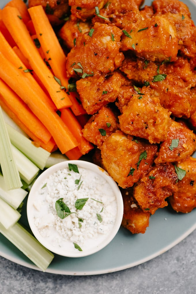 Buffalo chicken bites with carrot and celery sticks and blue cheese dressing on a blue platter.