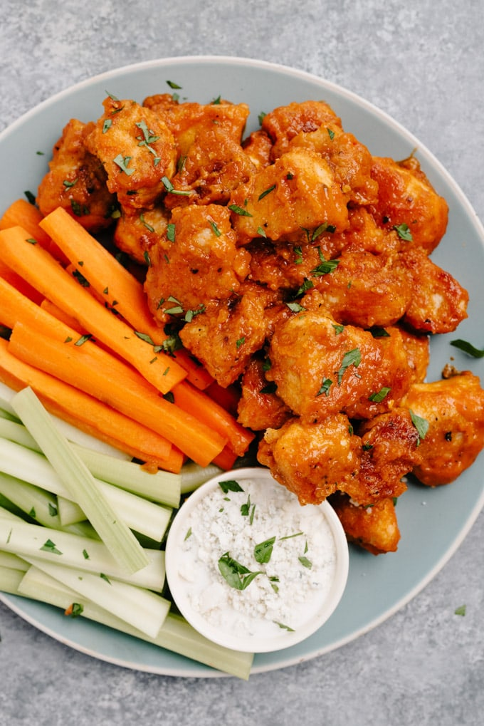 A platter of crispy pan fried buffalo chicken bites with a small bowl of blue cheese dressing and celery and carrot sticks.