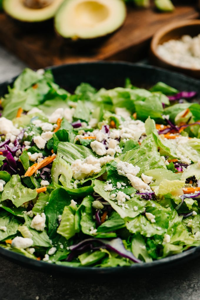 Side view of buffalo chicken salad base with romaine lettuce, shredded cabbage, carrots, celery, and blue cheese crumbles.