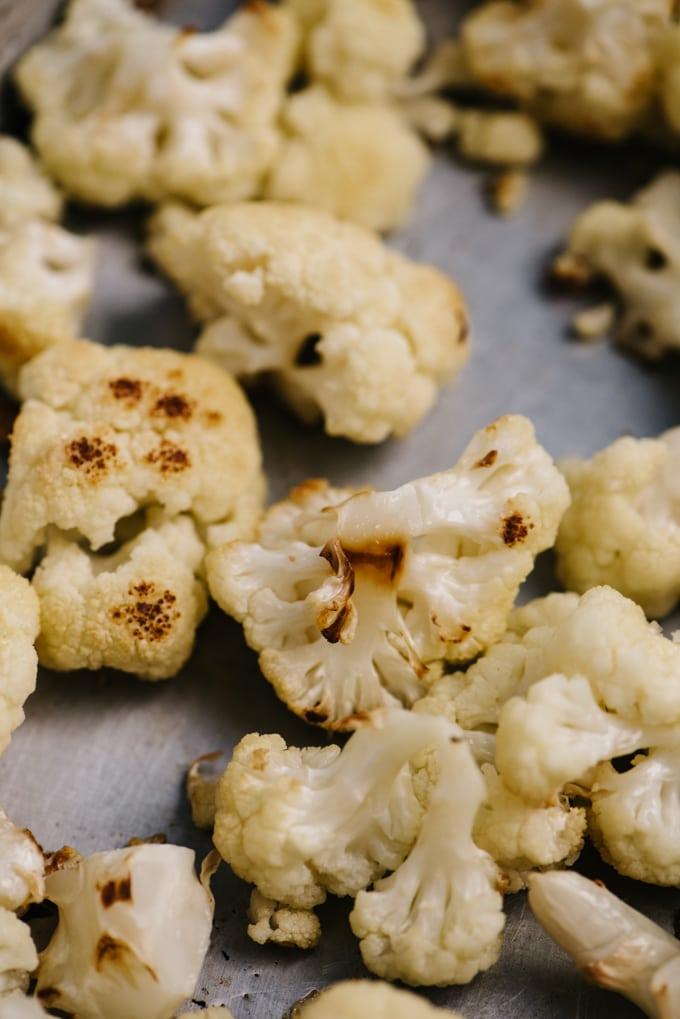 Detail shot of roasted cauliflower florets on a baking sheet.