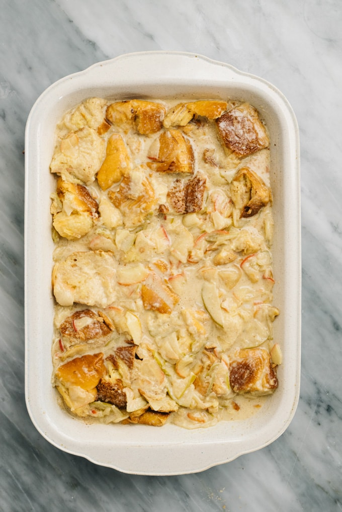 Unbaked apple bread pudding in a casserole dish.