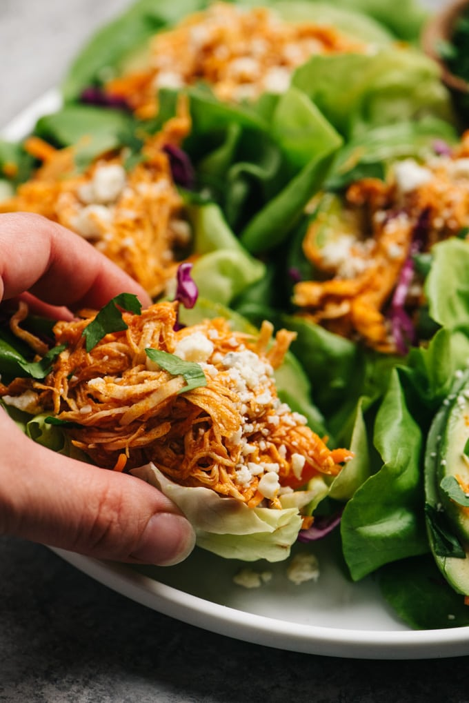 A woman's hand picking up a buffalo chicken lettuce wrap from a platter.
