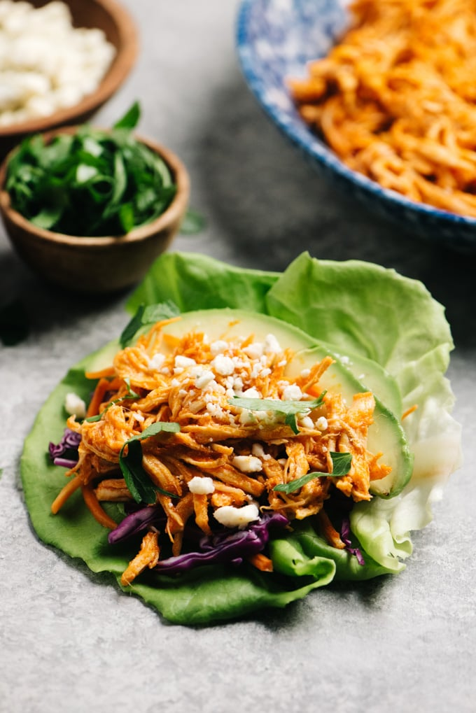 A prepared buffalo chicken lettuce wrap on a cement table top.