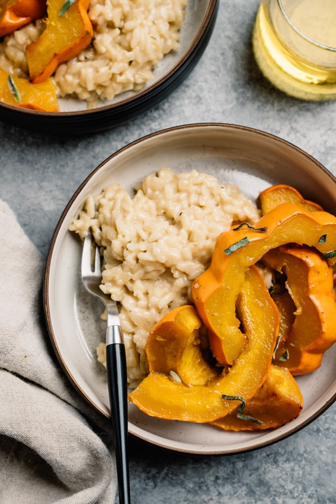 A bowl of roasted acorn squash over risotto on a cement background with a glass of white wine.