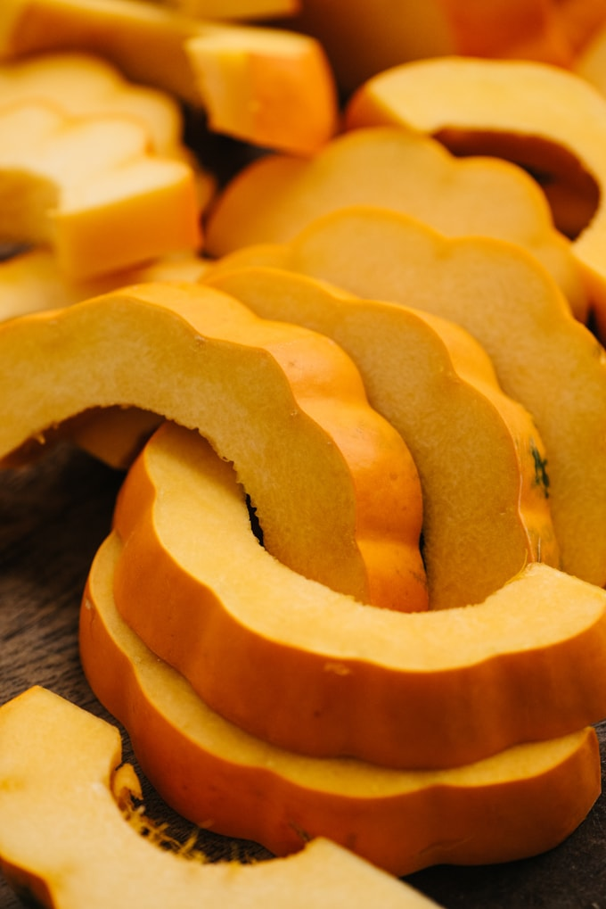 Acorn squash slices on a cutting board in a post on winter squash recipes.