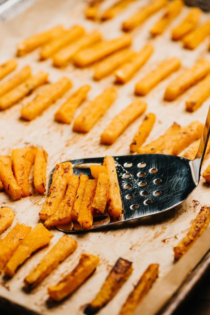 A metal spatula lifting baked butternut squash fries from a baking sheet.