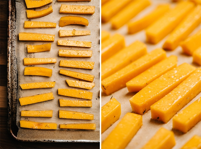 Butternut squash fries seasoned with thyme and salt on a baking sheet before being placed into the oven.