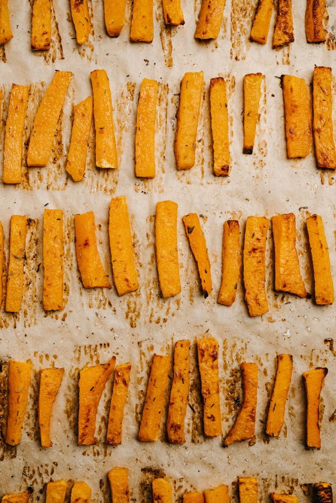 Oven baked butternut squash fries on a baking sheet.