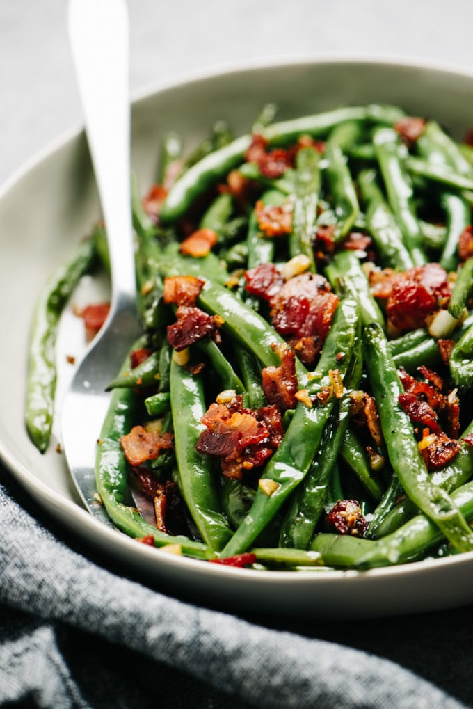 Side view, green beans with bacon in a serving dish with a silver serving fork.